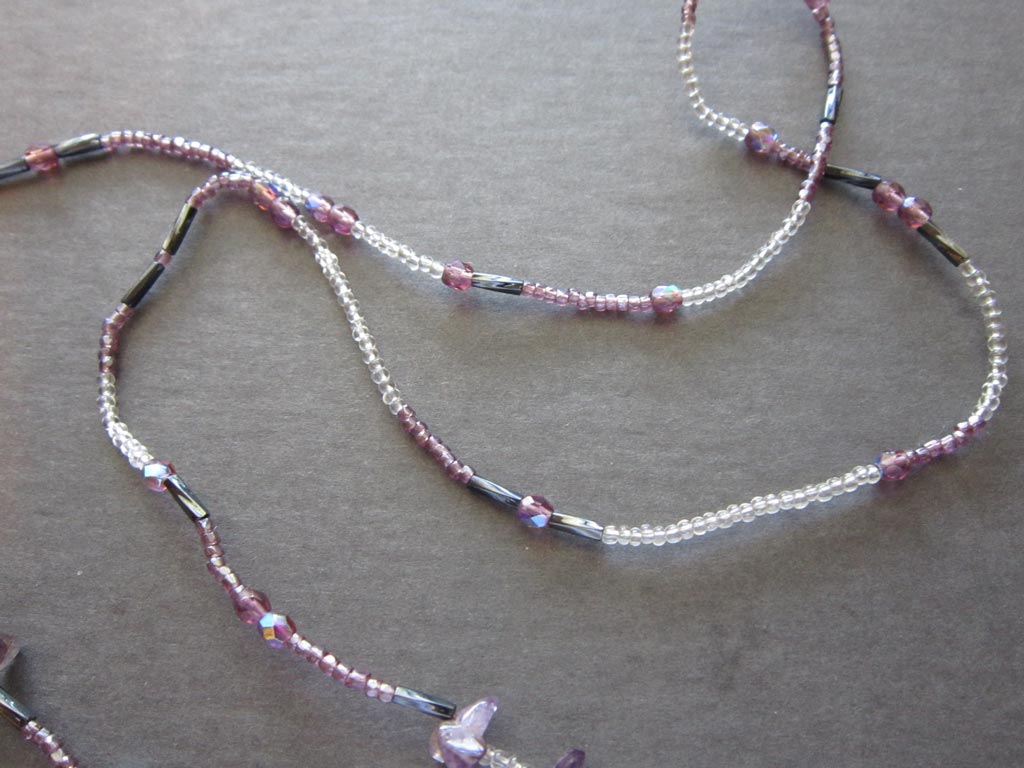 Closeup of beaded cord with various types of  beads, crystals and gemstones